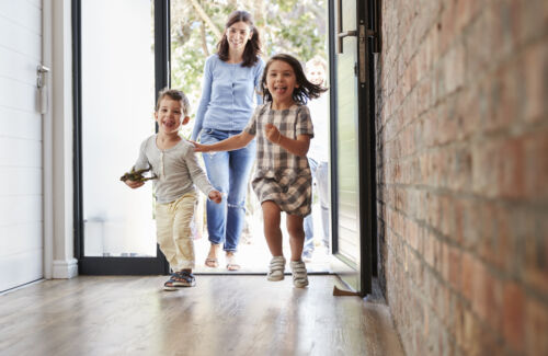 crianças animadas chegando em casa com os pais